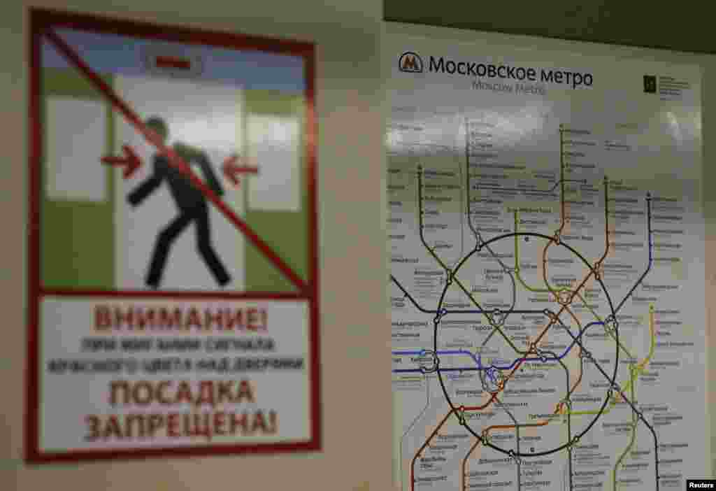 A map of the Moscow metro system is seen behind a poster warning passengers to avoid the closing doors on the train.