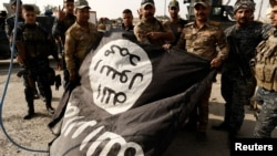 Iraqi soldiers pose with an Islamic State flag in the recaptured town of Al-Shura, south of Mosul, on October 30.