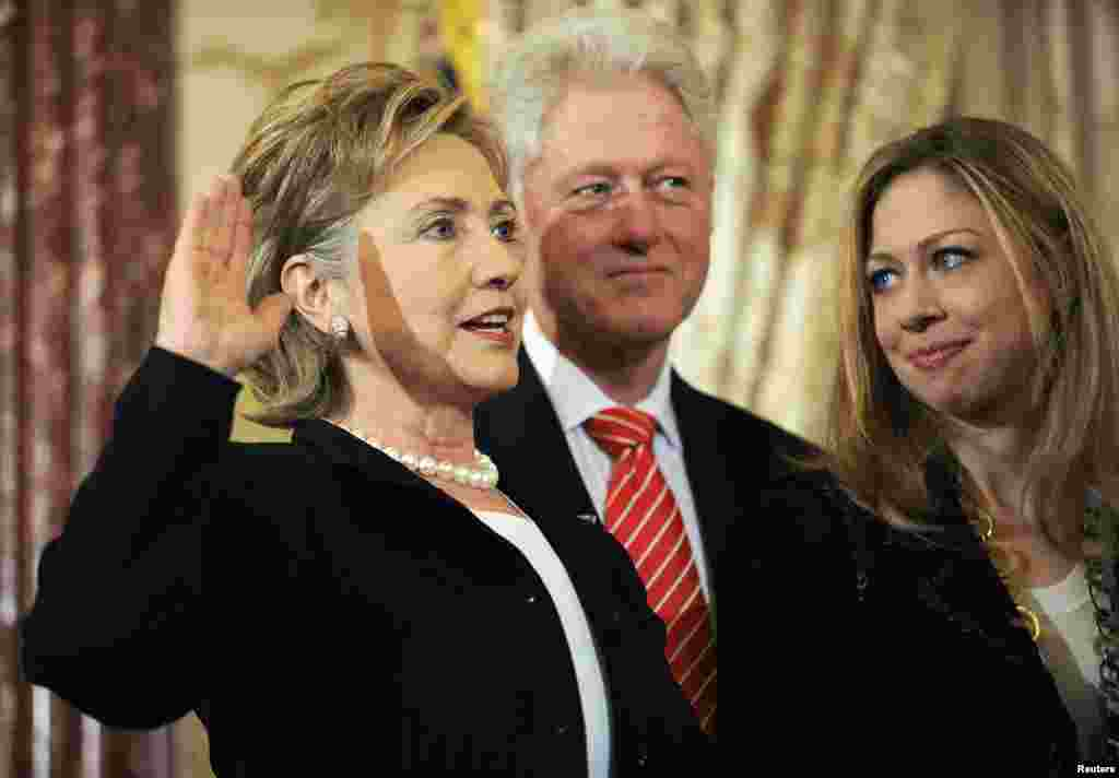Hillary Clinton (left) is joined by her husband, former U.S. President Bill Clinton (center), and daughter, Chelsea Clinton (right), as she is ceremonially sworn in as secretary of state at the State Department in Washington on February 2, 2009.