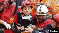 تصویر امدادگران پس از نجات عذرا، دختر نوزاد و دو هفته ای از زیر آوار. دوساعت بعد از نجات او، مادر و مادربزرگش هم از زیر آوار نجات یافتند.