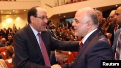 Iraqi Vice President Nuri al-Maliki (left) and new Prime Minister Haidar al-Abadi shake hands during the session to approve the new government in Baghdad in September 2014.