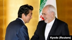 Japanese Prime Minister Shinzo Abe greets Iranian Foreign Minister Mohammad Javad Zarif at the start of their bilateral meeting in Yokohama, August 28, 2019