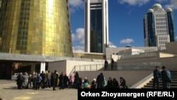 """Полицейские наблюдают за собравшимися """"ипотечниками"""" у правительственных зданий в Астане. 2 октября 2013 года."""
