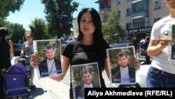 Ирина Титовская держит портреты застреленного Дмитрия Яковенко. Талдыкорган, 16 августа 2015 года.
