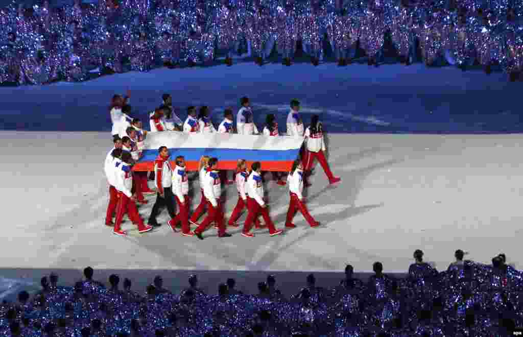 The Russian flag is carried into the stadium. (EPA/Barbara Walton)