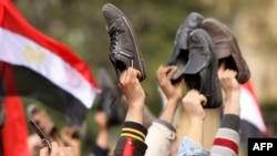 Antigovernment protesters wave their shoes outside the state television building in Cairo in February 2011 during protests that led to the ouster of President Hosni Mubarak.