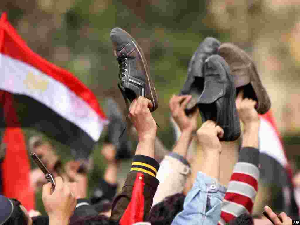 مخالفان کفشهای خود را در مخالفت با روش تلویزیون دولتی مصر بر سر دست بردهاند