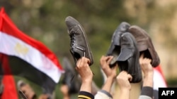 Antigovernment protesters wave their shoes outside a state building in Cairo,