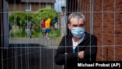 A Romanian worker stands behind a fence that was set up at the entrance of housing for Romania slaughterhouse workers in Rosendahl, Germany, on May 12.
