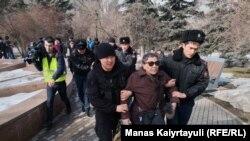 Полицейские уводят женщину, пришедшую на площадь Астана. Алматы, 22 февраля 2020 года.
