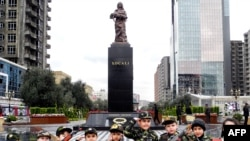 "Azerbaijan -- Wearing army-style camouflage costumes little Azerbaijanis take part in a ceremony to mark 21st anniversary of what Azerbaijan refers to as the ""Khojaly Massacre"" at a monument to the Khojaly victims in Baku, 25Feb2013"