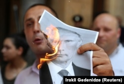 Учасники протесту у Тбілісі палили портрети президента Росії Путіна. Грузія, 20 червня 2019 року