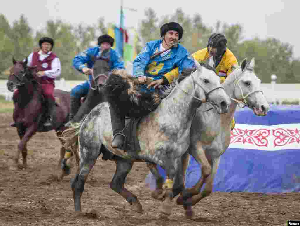 Riders from the teams from Kazakhstan (blue) and Tajikistan (yellow) compete in a match in Astana on September 11, 2013.
