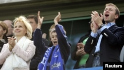 Chelsea owner Roman Abramovich (right) celebrates the team winning the English Premier League soccer trophy with his wife, Irina (left), and their son at Stamford Bridge in London in May 2007.
