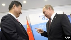 Russian President Vladimir Putin (right) chats with his Chinese counterpart Xi Jinping before the G20 summit in St. Petersburg late last year.
