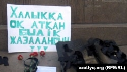 Тәуелсіздік ескерткіші алдына қойылған гүл шоқтары мен талап-жазу. Алматының орталық алаңы, 6 қаңтар 2012 ж.