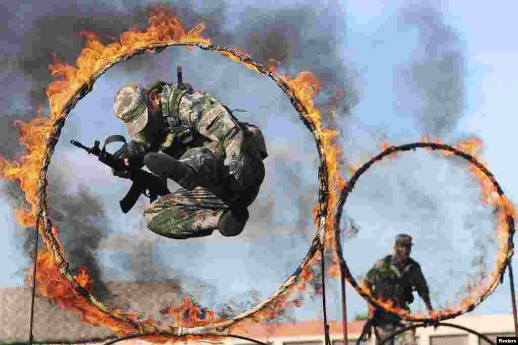 Soldiers from the Chinese People's Liberation Army jump through rings of fire as part of training during the PLA Army Day in Wenzhou, Zhejiang Province. (Reuters/Stringer)