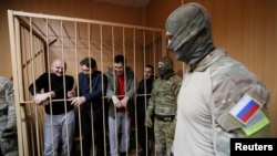 Captured Ukrainian sailors, await trial in Moscow last month.