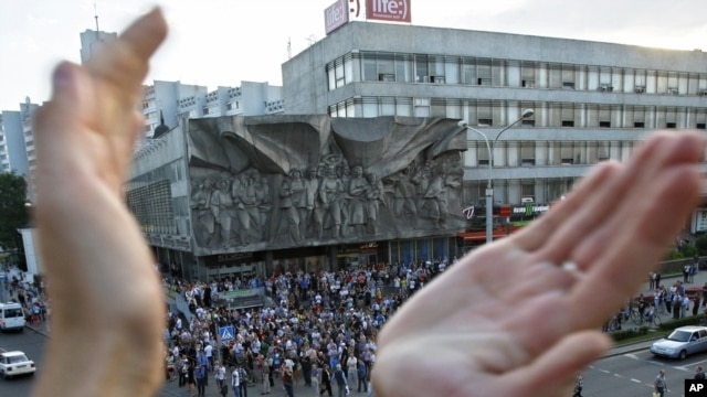 A protester applauds as people gather during a demonstration in Minsk organized via social networks.