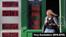 RUSSIA -- A woman leaves exchange office with an electronic panel displaying currency exchange rates for U.S. dollar and euro against Russian ruble in Moscow, August 23, 2018