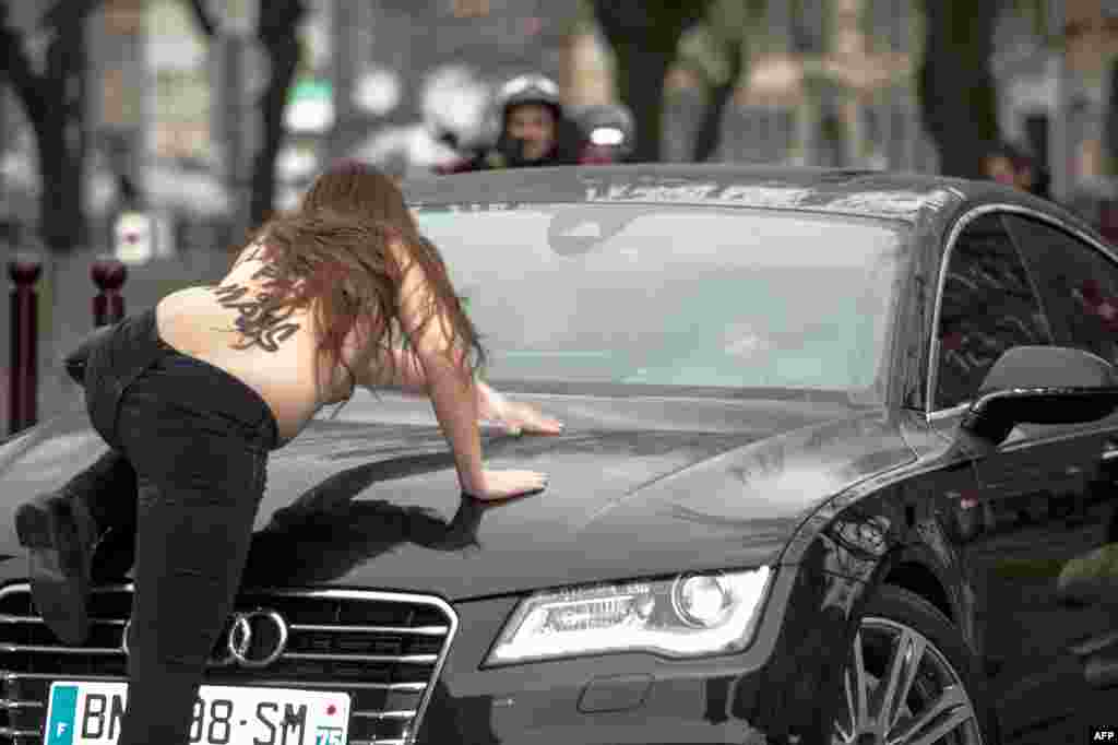 """A topless Femen activist jumps on the car carrying former IMF chief Dominique Strauss-Kahn (not seen) as he arrives for his """"aggravated pimping"""" trial in Lille on February 10. (AFP/Denis Charlet)"""