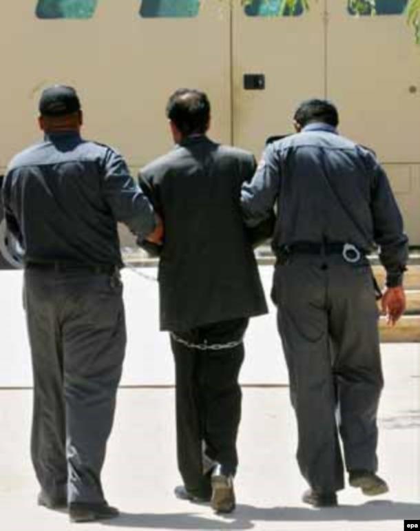 صدام را پس از جلسه محاکمه به سلول میبرند.