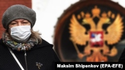 A woman wearing a protective face mask walks next to a Russian coat of arms at the Kalanchyovskaya railway station in Moscow on March 19.
