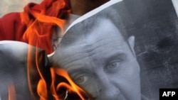 Один из сожженных протестующими снимков Башара Асада