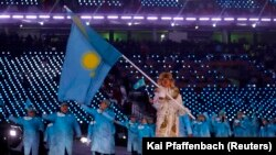 Шорт-трекист Абзал Ажгалиев с флагом Казахстана на открытии Олимпиады в Пхёнчхане. 9 февраля 2018 года.