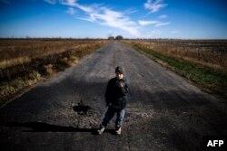 Хлопчик показує шматок шрапнелі біля села Набережне (Новоазовський район). Жовтень 2014 року