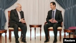 Syrian President Bashar al-Assad (right) meets with Iranian Foreign Minister Mohammad Javad Zarif in Damascus on January 15.