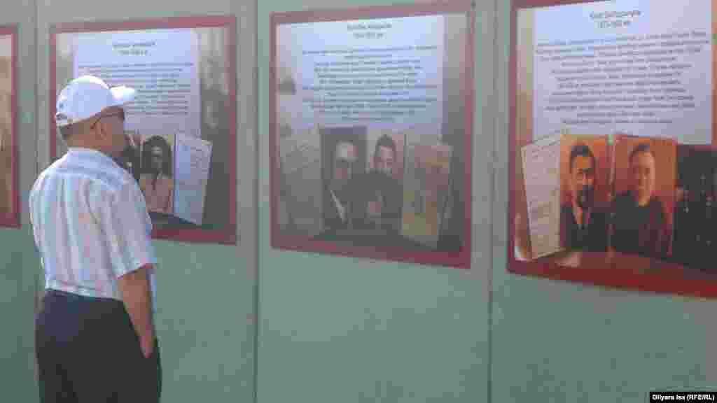 Мемориал ішінде Алаш зиялыларының биографиясы жазылған тақтайшаны тамашалап тұрған тұрғын. Шымкент, 31 мамыр 2016 жыл.