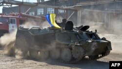 A serviceman of the volunteer Donbas Battalion practices driving an armored personnel carrier on July 28 captured from pro-Russian militants in the Ukrainian city of Lisichansk near Luhansk.