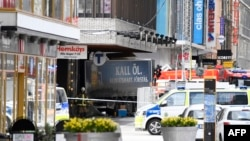 Emergency services work at the scene where the truck crashed into the Ahlens department store in central Stockholm.