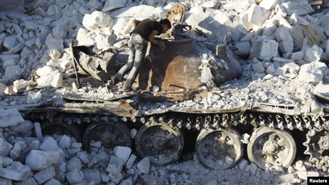 A man inspects a destroyed Syrian Army tank in Azaz, some 47 kilometers north of Aleppo.