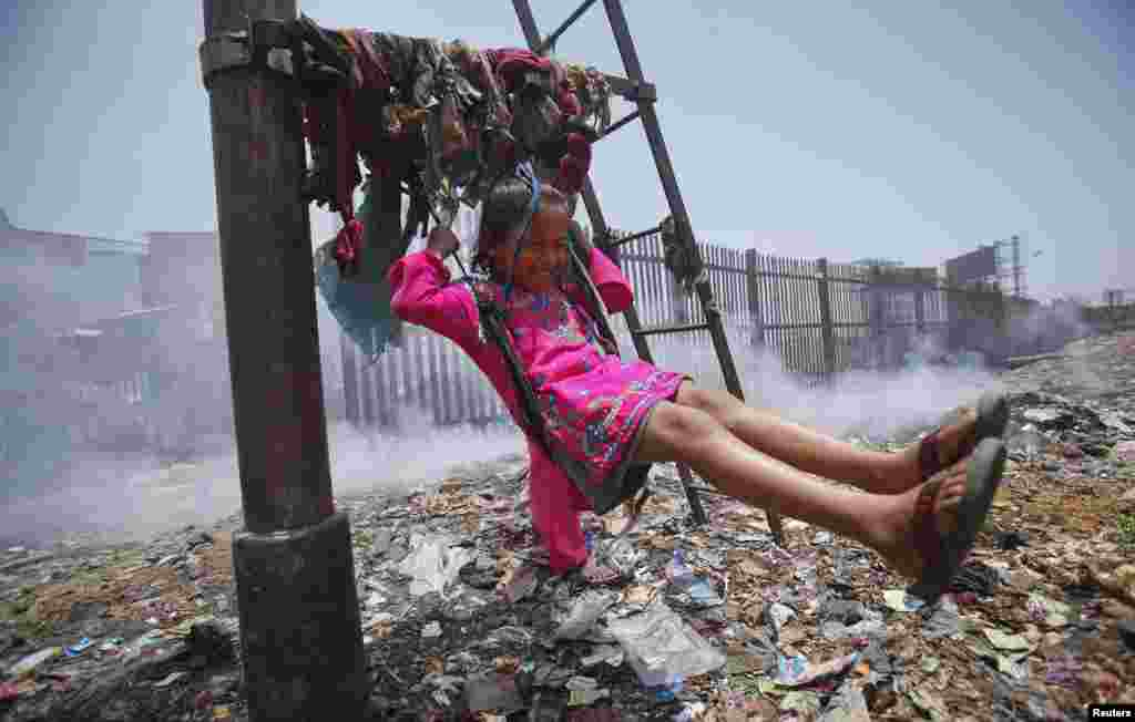 Sana, 5, plays on a cloth sling hanging from a telephone pole as smoke from a garbage dump rises next to a railway track in Mumbai, India.
