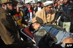 Pakistani rescuers move an injured man into a hospital in Charsadda.