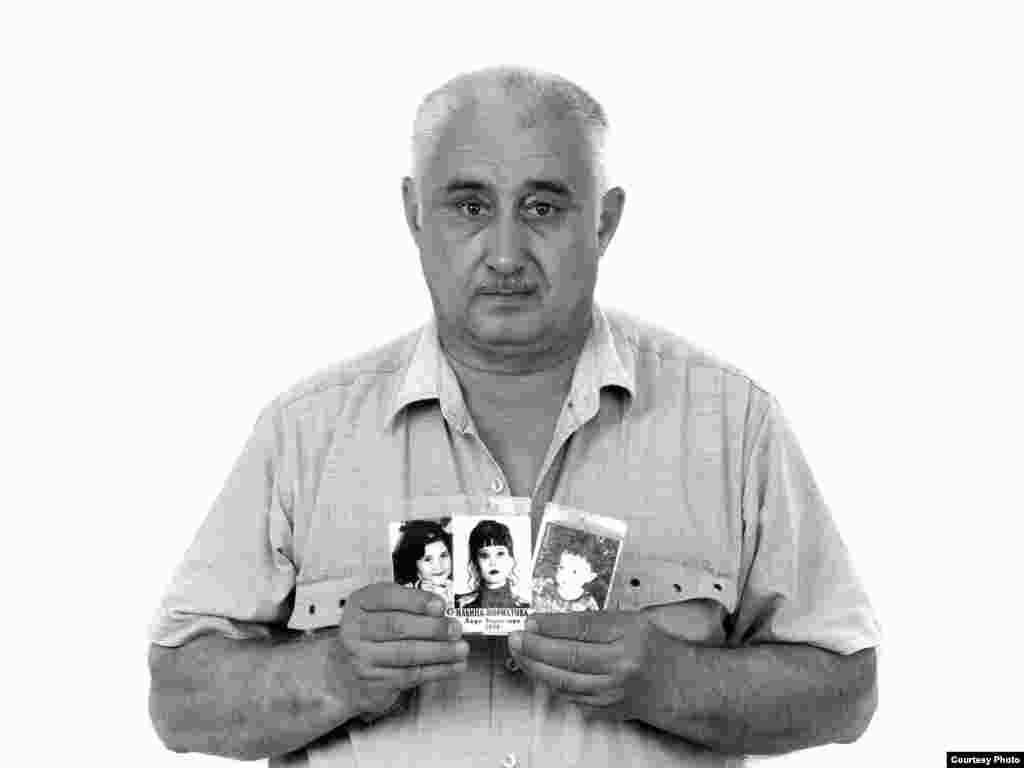Boris Ilyin, holding photographs of his granddaughter Zarina, his daughter Elvira, and his grandson Amirkhan - Boris Ilyin brought his family from Tashkent to Ossetia to visit their historic homeland two weeks before the siege. The family decided that they should let their first-grader, Zarina, go to school in Beslan during their stay so she wouldn't miss too much of the school year. On September 1, 2004, Boris's daughter Elvira took Zarina, her 4-year-old son Amirkhan, and their 8-year-old cousin Georgy to school. Georgy was the only one who survived.