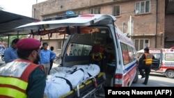 Пәкістанда ұшақ апатынан қаза болған адамды дәрігерлер көлікке салып жатыр. Равалпинди қаласы, 30 шілде 2019 жыл.