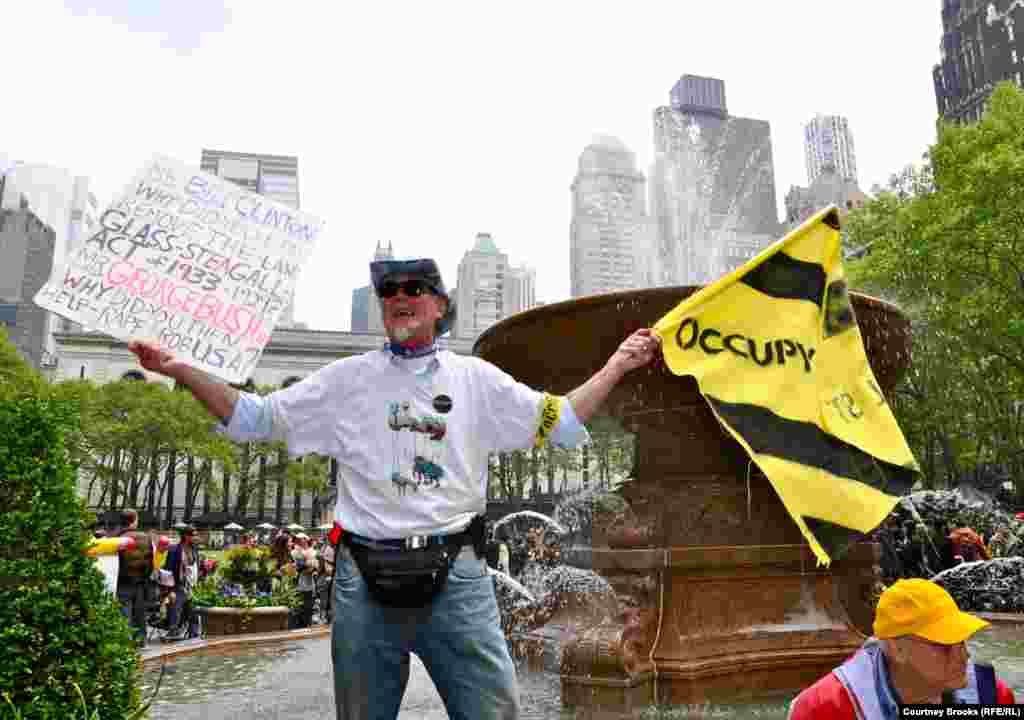 A protester stood on Bryant Park's fountain and shouted that both the Democratic and Republican parties are guilty of corruption and greed.