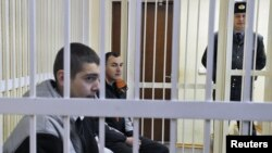 Russian political activists Ivan Gaponov (left) and Artyom Breus sit in the dock during a court hearing in Minsk on February 22.