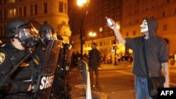 "An ""Occupy Oakland"" protester who as part of the ""Occupy Wall Street"" movement stands in front of the police line as the police block streets in downtown Oakland on October 25."