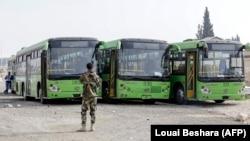 Автобуси чекають на жителів Східної Гути, які залишають регіон, біля пропускного пункту Вафідін, Сирія, 13 березня 2018 року