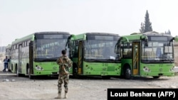 Buses wait to evacuate civilians on the government side of the Wafideen checkpoint on the outskirts of the Syrian capital Damascus, near the eastern Ghouta enclave on March 13.