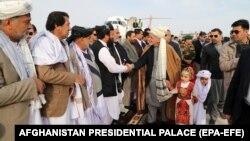 AFGHANISTAN -- A handout photo made available by Afghanistan's Presidential Palace shows Afghan President Mohammad Ashraf Ghani (Center) greets Nimroz province government authorities after arriving to inaugurate the country's first export convoy of goods