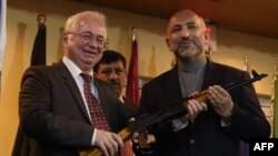 FILE: Russian Ambassador to Afghanistan Aleksandr Mantytsky (L) hands over a AK-47 rifle to Afghan National Security Adviser Hanif Atmar during a ceremony at a military airfield in Kabul in February.