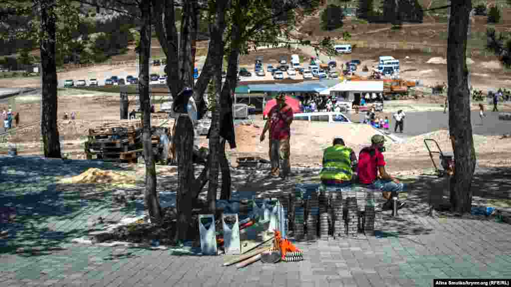 Работники заканчивают укладку плитки на месте снесенных торговых палаток на вершине плато