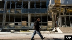 A man walks past a building damaged in recent shelling in Donetsk's Kyivskiy district, near the airport, on October 7.