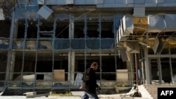 A man walks past a building damaged in recent shelling in Donetsk's Kyivskiy district near the airport on October 7.