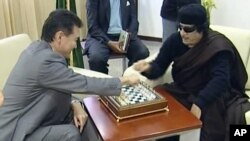 Staving off what many expected would be a quick checkmate has become something close to victory for Libya's Muammar Qaddafi (right).